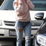 Con jeans rotos y hoodie